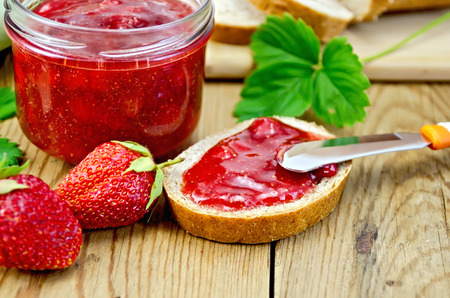Bread with strawberry jam, a jar of jam, knife, strawberries on a wooden boards background