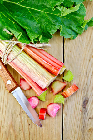 Bundle of stalks of rhubarb leaf and cut pieces of rhubarb, knife on background wooden plank photo