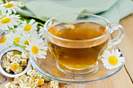 Herbal tea in a glass cup, metal sieve with dry chamomile flowers, fresh flowers, daisies, green cloth on a background of wooden boards photo