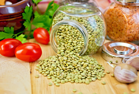Lentils green in glass jar, parsley, garlic, tomatoes, clay pot, napkin on the background of wooden boards photo
