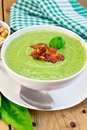 Green soup puree in a white bowl with spinach and grilled meat, napkin, crackers, spoon on a wooden boards background photo