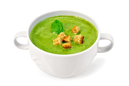 Green soup puree in a white bowl with croutons and spinach leaves isolated on white background Stock Photo