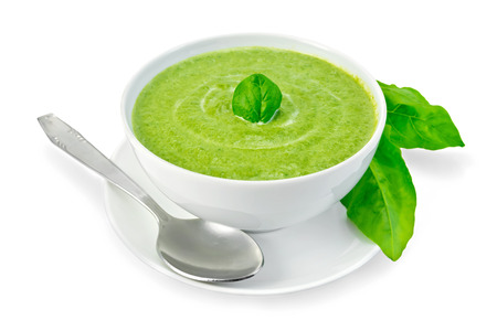 Cream soup green from spinach in a white bowl with leaf spinach on a plate, spinach leaves isolated on white background