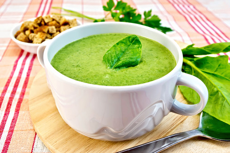 cream and green: Green soup puree in a bowl with green leaf spinach, spoon on the board, croutons, parsley on a cloth background