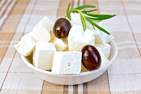 Feta cheese, olives, rosemary in a white bowl on a background of brown tablecloth