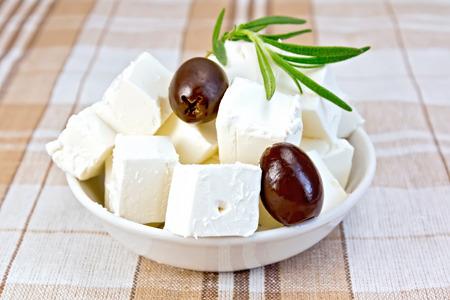 Feta kaas, olijven, rozemarijn in een witte kom op een achtergrond van bruin tafelkleed