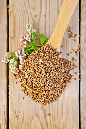 Buckwheat in a spoon with flower buckwheat on a wooden boards background photo