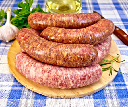 Raw pork and beef sausages on a round wooden board, knife, rosemary, parsley and garlic on a background of blue plaid fabric photo
