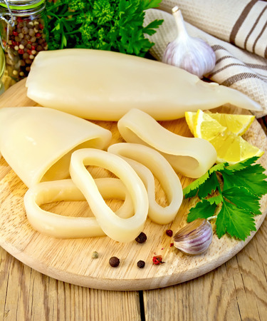 Whole and sliced squid rings, lemon, garlic, pepper, parsley, napkin nafone wooden board