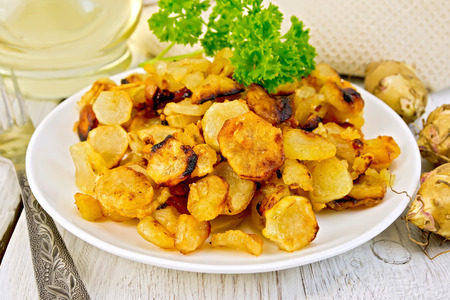 Jerusalem artichokes fried in a dish, fresh tubers, napkin, parsley, vegetable oil on a background of white wooden plank