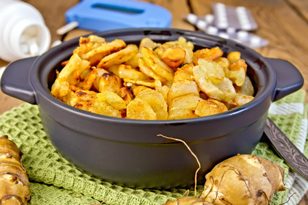 Jerusalem artichokes roasted in a roasting pan, fresh tubers on a napkin, the meter and pills on the background of wooden boards