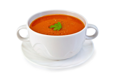 Tomato soup in a white bowl with parsley on a plate isolated on white background Standard-Bild