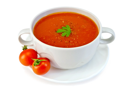 Tomato soup in a white bowl with parsley on a plate with tomatoes isolated on white background