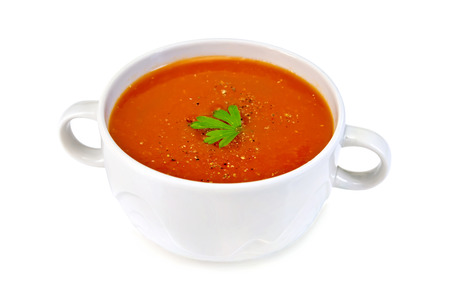 Tomato soup in a white bowl with parsley isolated on white background