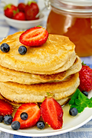 Flapjacks with strawberries and blueberries on linen tablecloth photo