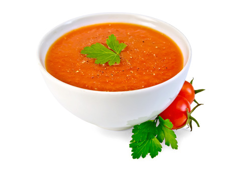 Soup tomato in white bowl with parsley and tomatoes