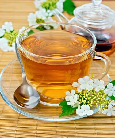 Tea from flowers of viburnum on bamboo napkin photo