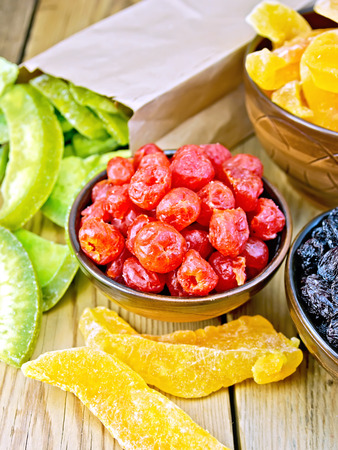 Candied cherries and other fruit in bowl on board photo