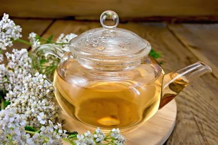 milfoil: Tea with yarrow in glass teapot on board Stock Photo