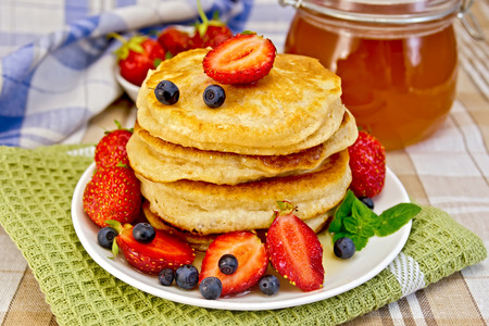 flapjacks: Flapjacks with strawberries and blueberries with napkin Stock Photo