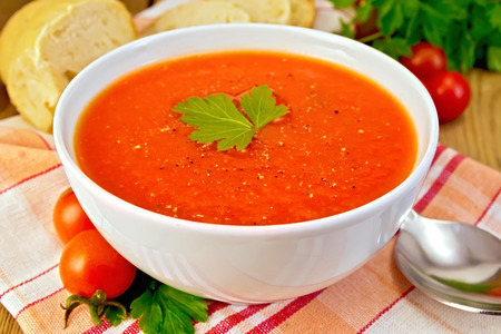 tomato soup: Tomato soup in bowl on napkin with bread