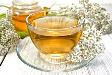 Tea with yarrow in cup on light board