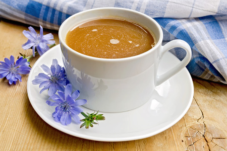 chicory coffee: Chicory drink in a white cup with a flower napkin on a wooden boards background