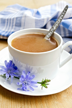 chicory coffee: Chicory drink in a white cup with a flower and a spoon, napkin on a wooden boards background