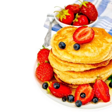 flapjacks: Flapjacks with strawberries and blueberries in bowl with napkin Stock Photo