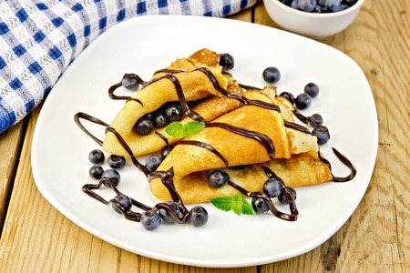 rubicund: Pancakes with blueberries and chocolate on board