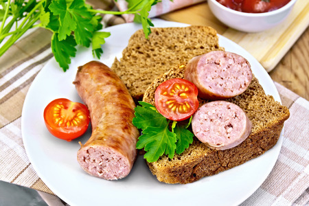 Sausages fried with bread and tomato in plate photo