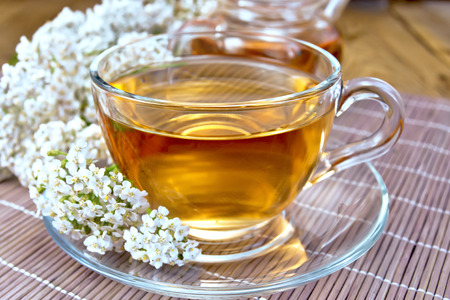 milfoil: Tea with yarrow in cup on bamboo napkin Stock Photo