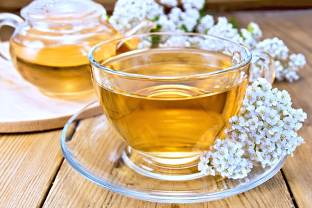 Tea with yarrow in cup on board Stock Photo