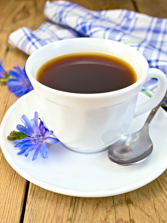 chicory coffee: Chicory drink in a white cup with a spoon and a flower on a saucer, a blue checkered cloth on a wooden board