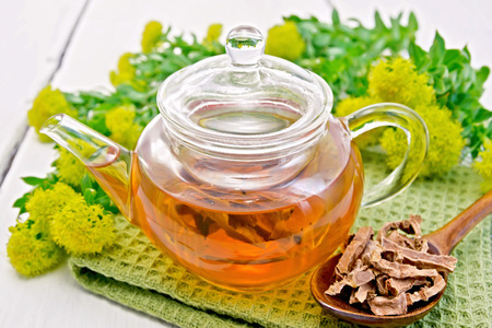 Herbal tea in a glass teapot on a napkin, spoon with dry roots of Rhodiola rosea, fresh flowers Rhodiola Rosea on the background light wooden boards