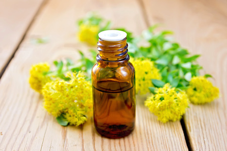 The oil in the bottle, flowers and leaves Rhodiola rosea on a wooden boards background