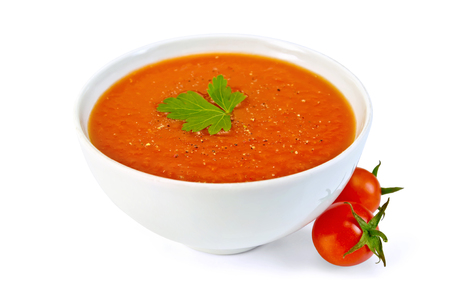 Tomato soup in a white bowl with parsley and tomatoes isolated on white background
