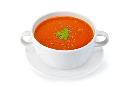 Tomato soup in a white bowl with parsley and spices on a saucer isolated on a white background Archivio Fotografico