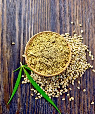 Hemp flour in a bowl, corn and green leaves of hemp on a background of wooden planks on top