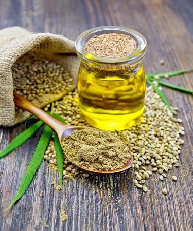 semilla: cáñamo harina en una cuchara de madera, semillas de cáñamo en una bolsa y una mesa, aceite de cáñamo en un tarro de cristal, hojas verdes de cáñamo en un fondo de tablones de madera