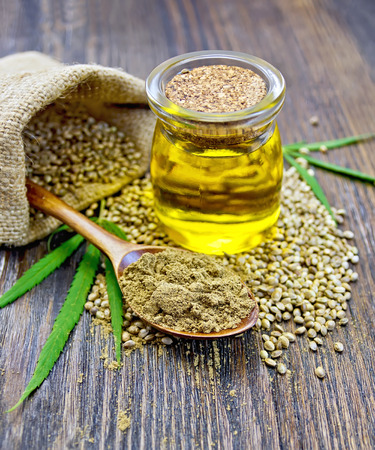 Flour hemp in a wooden spoon, hemp seed in a bag and table, hemp oil in a glass jar, green leaves of hemp on a background of wooden planks