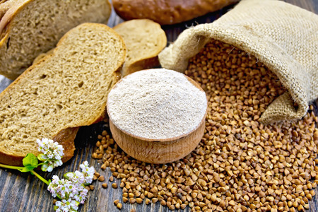 Buckwheat flour in a wooden bowl, buckwheat in the bag, slices of bread, buckwheat flower on the background of wooden boards