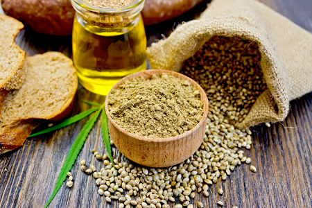 Hemp Flour in a wooden bowl, hemp seed in a bag and on the table, hemp oil in a glass jar, hemp leaf and bread on a wooden boards background