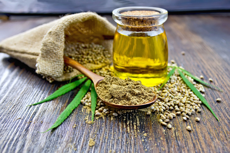 Flour hemp in a wooden spoon, hemp seed in a bag and on the table, hemp oil in a glass jar, hemp leaves on the background of wooden boards
