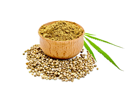 Hemp flour in a bowl, beans and green leaf of hemp isolated on white background