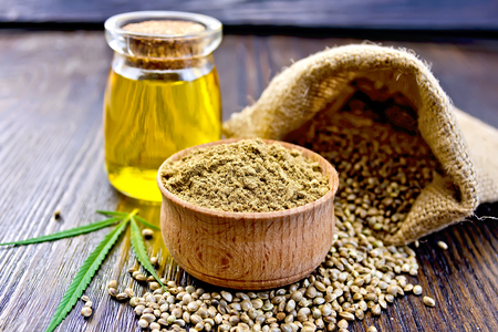 Hemp Flour in a wooden bowl, hemp seed in a bag and on the table, hemp oil in a glass jar, hemp leaf on the background of wooden boards