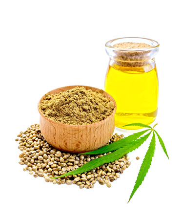 Hemp flour in a bowl, beans and green leaf of hemp, hemp seed oil in a glass jar isolated on white background