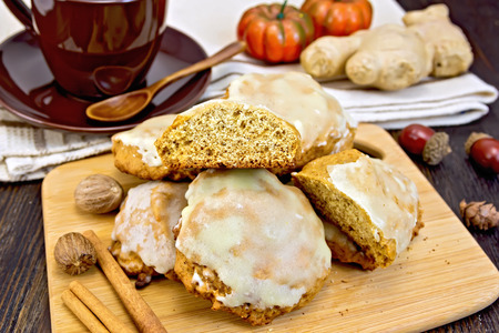 galletas de jengibre: Cookies pumpkin, nutmeg and cinnamon on the plate, brown cup, pumpkin, ginger on a napkin on a wooden boards background