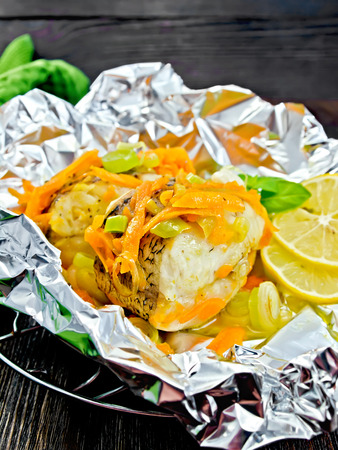 limnetic: Pike with carrots, leek, basil and lemon slices in a foil on a metal grid, a towel on the background of wooden boards Stock Photo