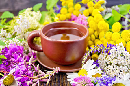 fireweed: Herbal tea in a clay cup of fresh flowers fireweed, tansy, chamomile, clover, yarrow, meadowsweet, mint leaves on a dark wooden board